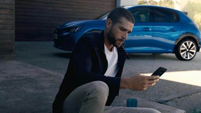 NUEVO PEUGEOT e-208 – Hombre con smartphone, Aplicación MyPeugeot